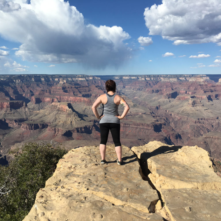 woman stands on cliff overlooking grand canyon