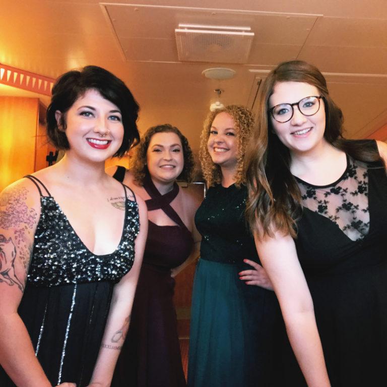 four smiling ladies dressed in black