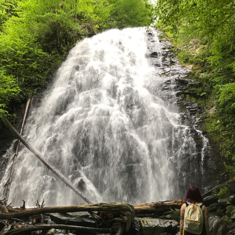woman standing in front of a large waterfall