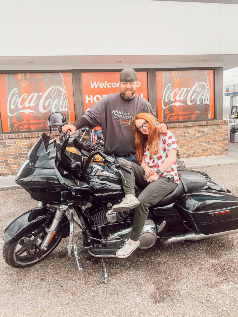 girl poses with harley davidson in front of coca cola signs