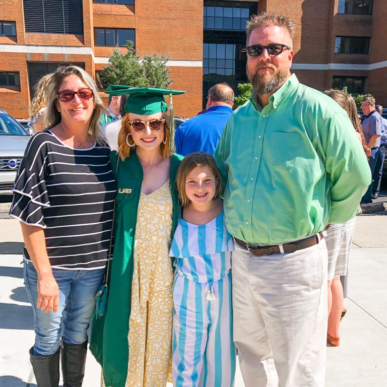 girl poses in uab cap and gown with family