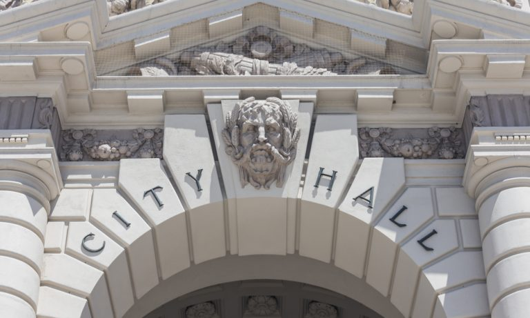 """stone archway with a man's bust and the words """"city hall"""" over it"""