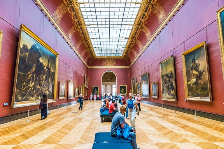 people walking around an art museum with multiple paintings displayed