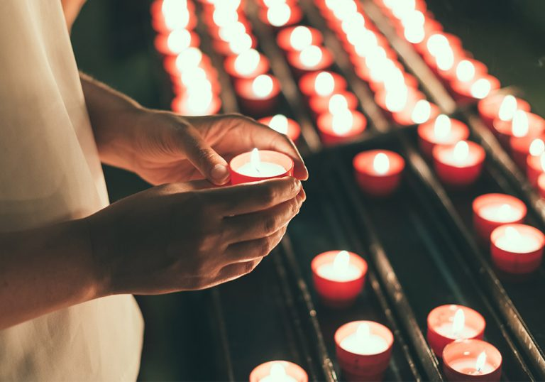 woman holds a lit votive candle in a church