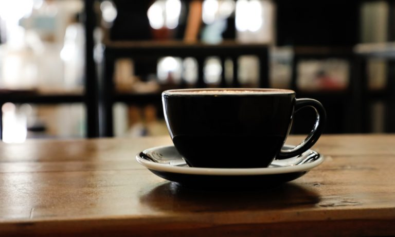cup of coffee on a wooden table with people in the background