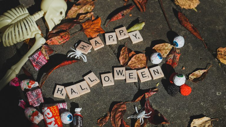 """scrabble tiles spelling out """"halloween"""" surrounded by candy"""