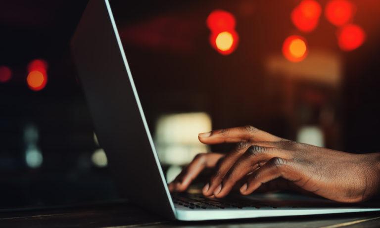 black man typing on a laptop keyboard