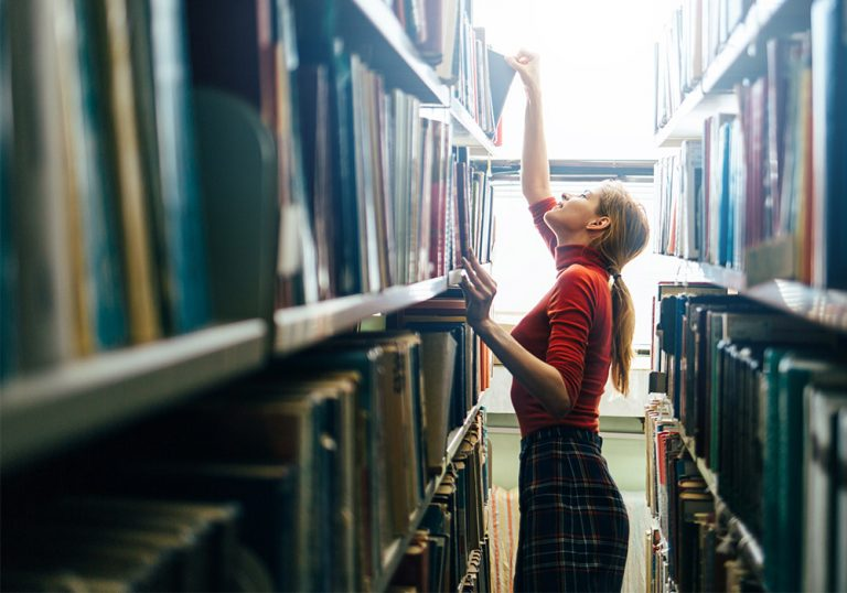 woman reaches for a book on a top shelf in a sunny library