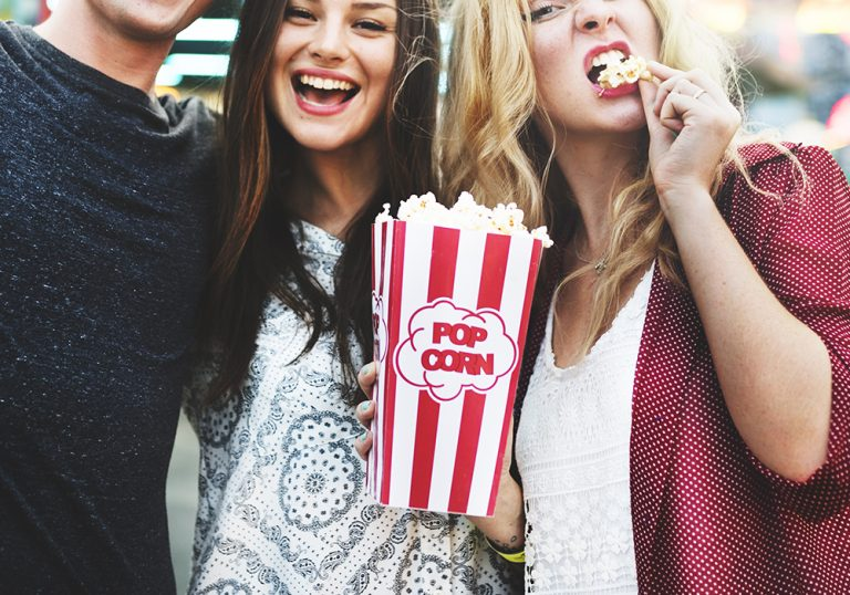 three young movie-goers share popcorn during a film festival