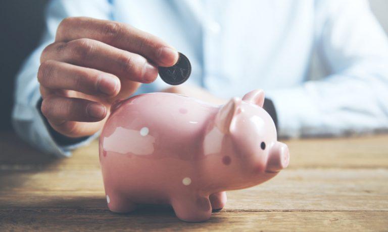 business man putting a coin into a piggy bank