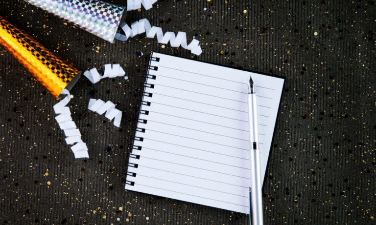 notebook with a pen surrounded by party streamers