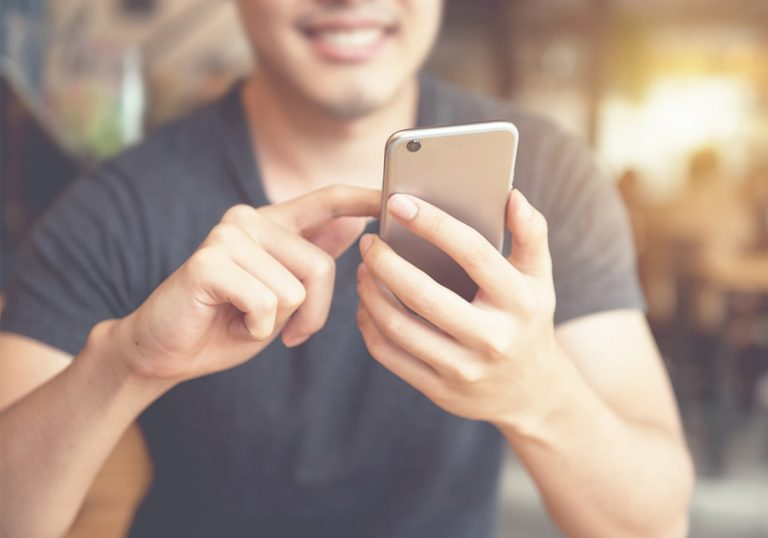 smiling man scrolls on mobile device