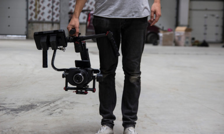 man holding a large videography camera