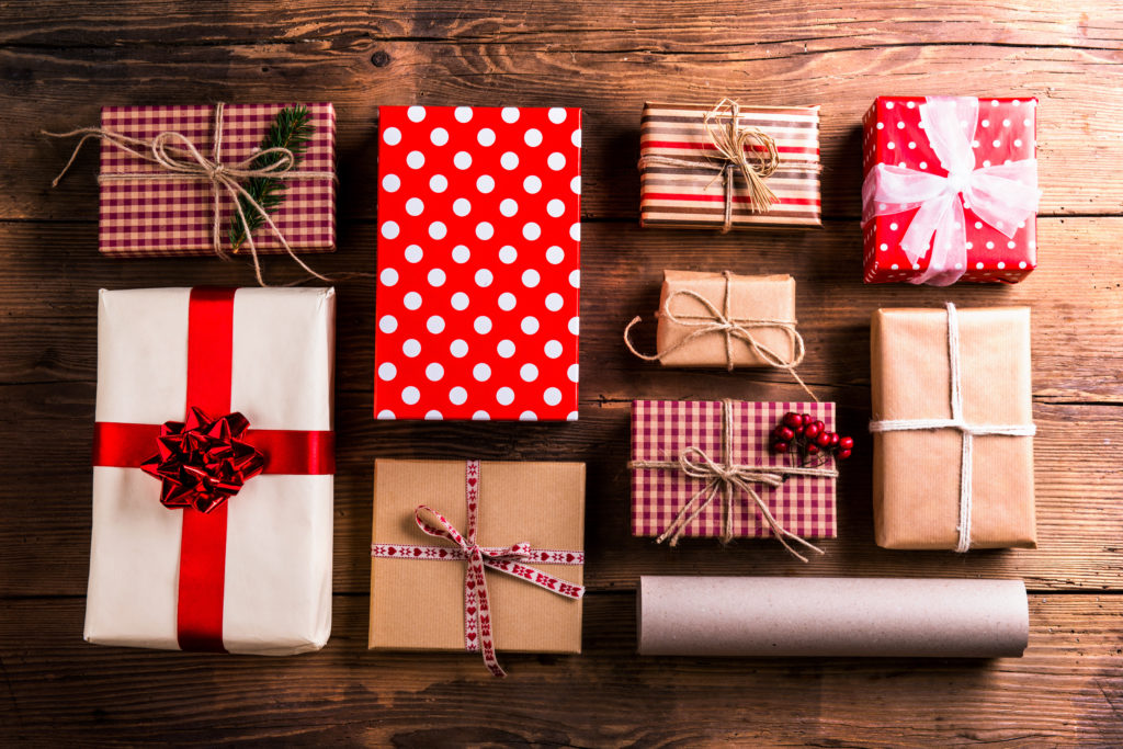 gifts wrapped for christmas sit on wooden table