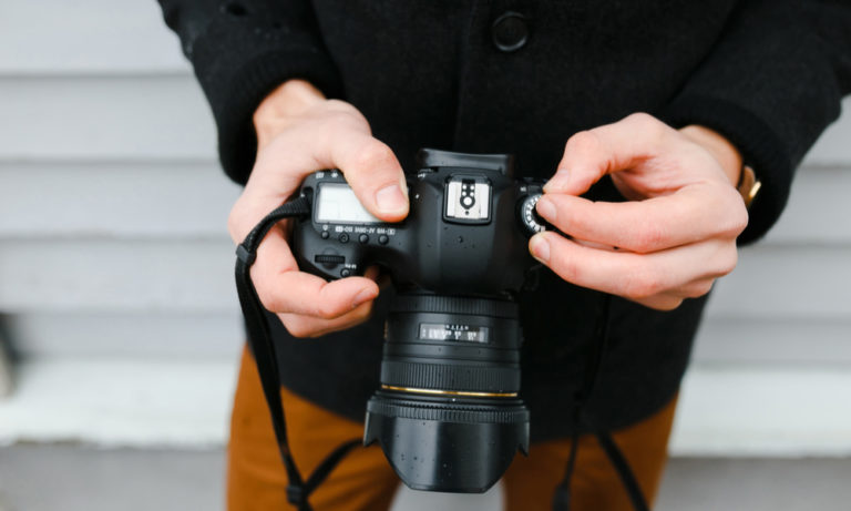 a man's hands adjusting the setting on his camera