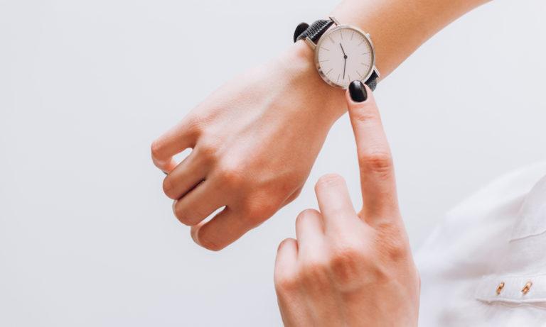 young woman checks her wrist watch