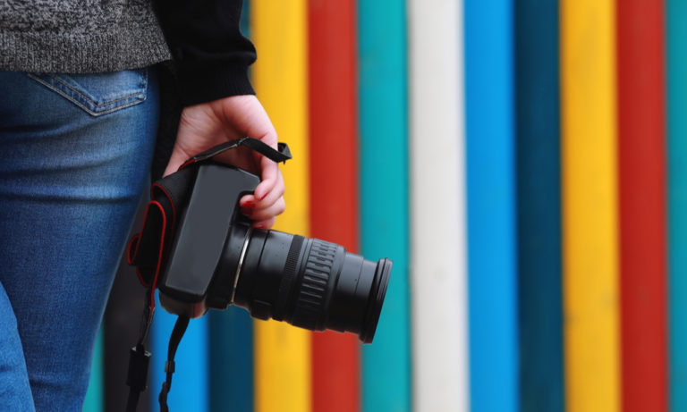 woman's hand holding a DSLR camera in front of a colorful striped wall