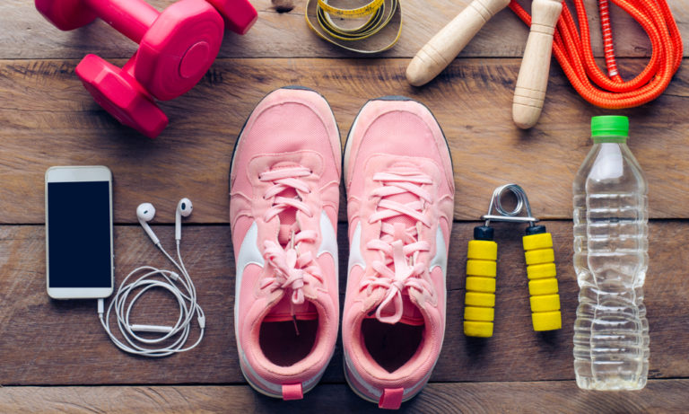 laid out exercise equipment like tennis shoes, weights, and earbuds