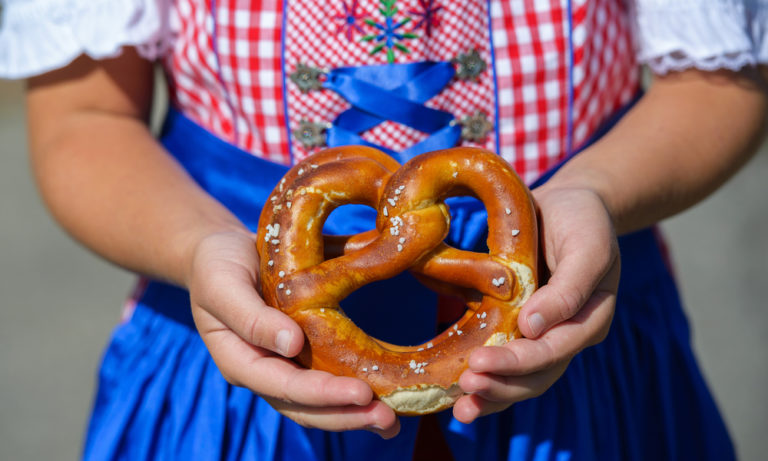 small girl wearing traditional German clothing holding a pretzel