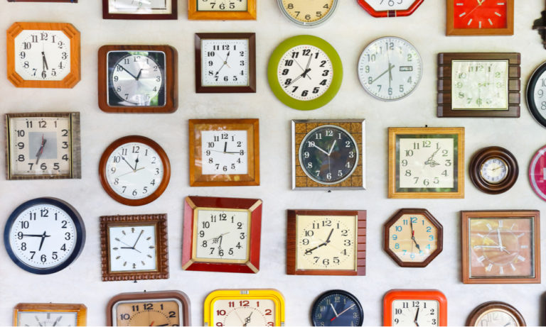 different shaped clocks hanging on a wall