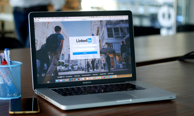 silver laptop on a table with linkedin open on the browser