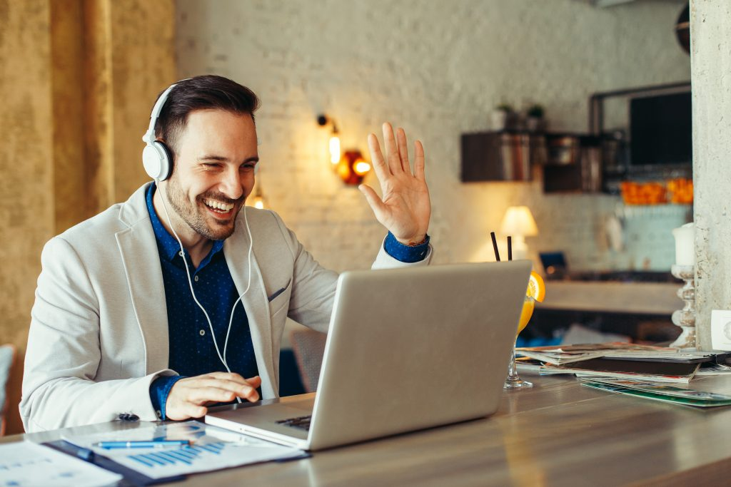 happy guy waves at a computer