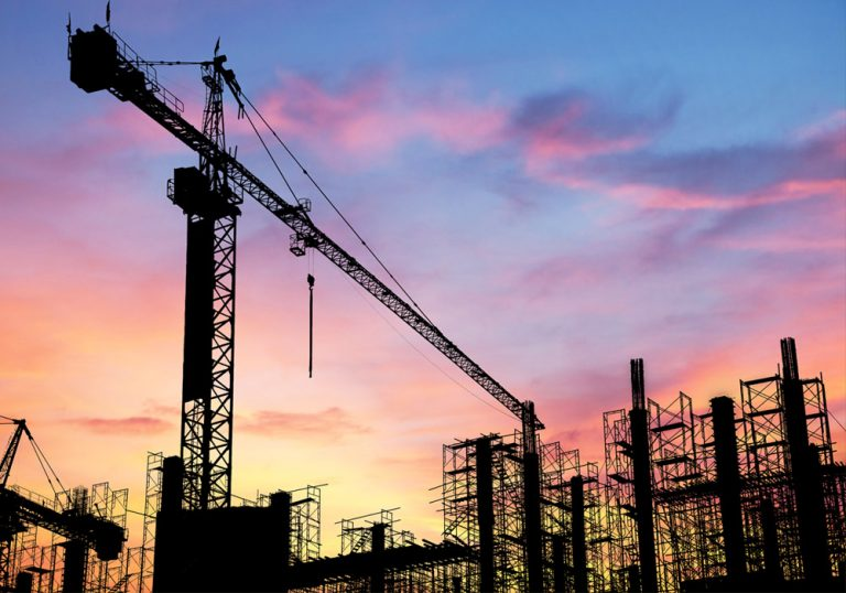 construction site silhouetted during a colorful sunset