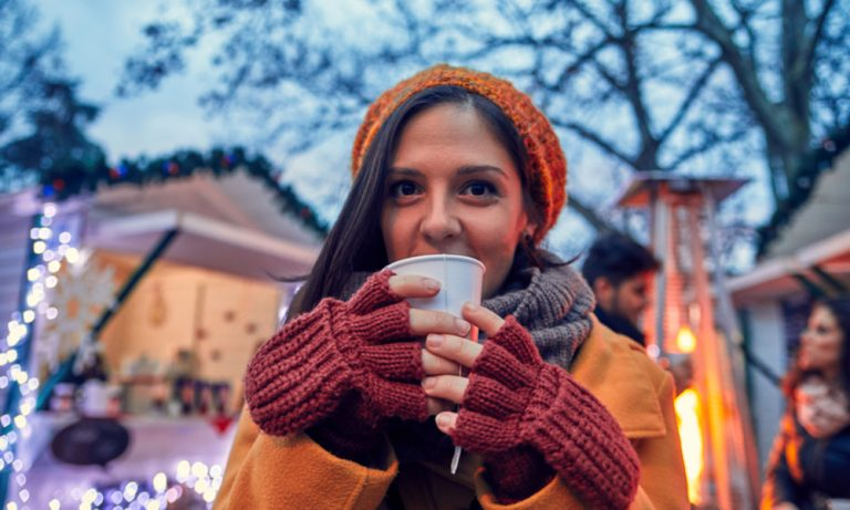 woman wearing winter clothing drink cocoa at a christmas market