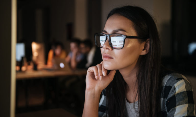 woman wearing glasses looking at a computer screen